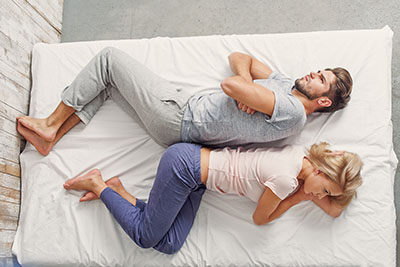 couples sleeping in separate beds