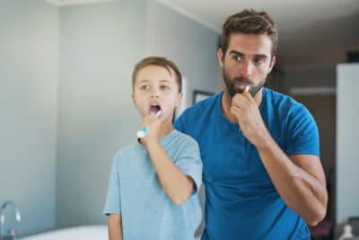 Cropped shot of a handsome young man and his son brushing their teeth in the bathroom