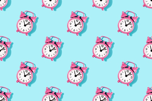 Seamless pattern made with vintage pink alarm clock on turquoise background. Flat lay, top view.