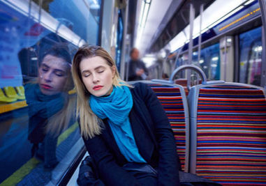 portrait of young woman sleeping inside subway train, feeling exhausted.lifestyle concept.