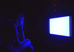sad caucasian woman watching tv at night